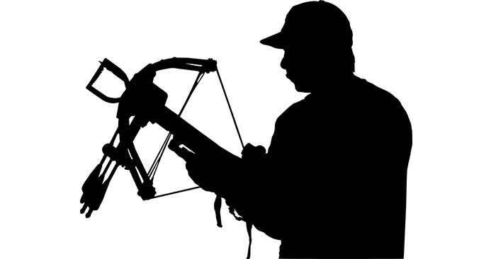 Silhouette of man ready to use his cross bow