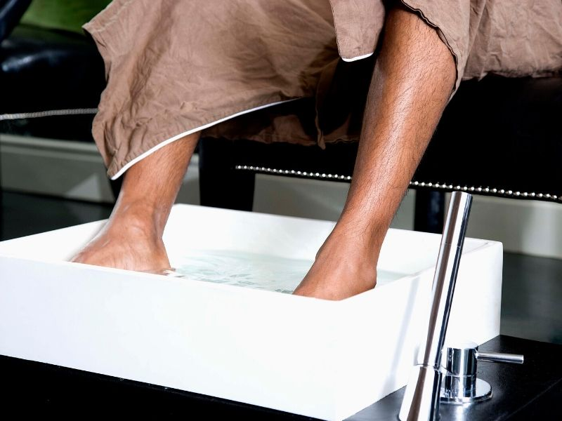 Man's feet soaking in vinegar and water soltution