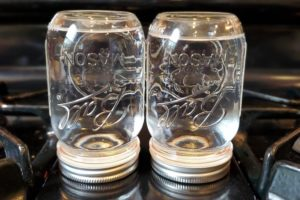 inverted mason jars with water ready for canning